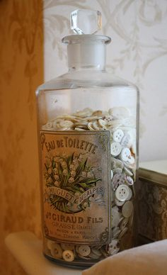 Vintage glass bottle filled with old pearl buttons ~