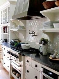 Luscious kitchens - mylusciouslife.com - White kitchen, standalone metal/black hood, floating shelves with corbels  carol reed design. I like the white kitchen shelving and racks units system for storage