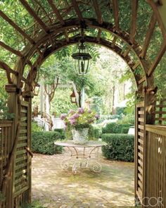 Wisteria covered trellis leading into garden.  Gorgeous!!