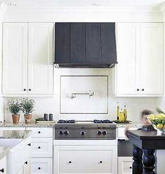 White cabinets, charcoal rangehood, dark timber table