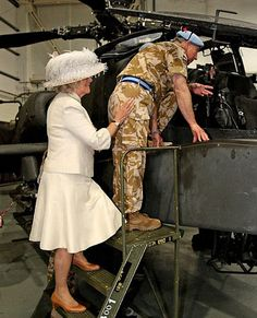 Camilla playfully pushes the POW into an oil tank as punishment for the blue beret and belt.