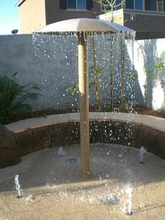 outdoor splash pad, backyard fun, umbrellas, pool, outdoor showers