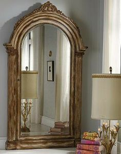 The Elizabeth Storage Mirror, set in a gorgeous wood frame with a multistep, bronze painted and distressed finish, rests on the floor and attaches to the wall for stability.