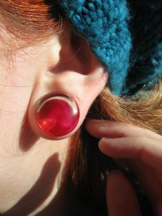 15mm clear glass plugs for stretched ears with red nail varnish on the backs