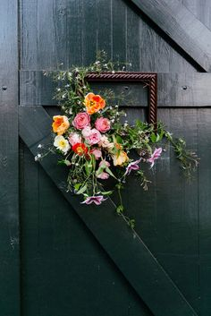 A wooden frame decorated with cascading flowers. Source: Tory Williams Photography. #weddingframes #framedecor