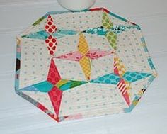 Star Drops Table Topper - If you want your star quilt patterns to stand out within your home decor, learn how to make a quilted table topper pattern like this. It's got a bit of retro pizzazz, and a unique quilted star design that will put your skills to the test.