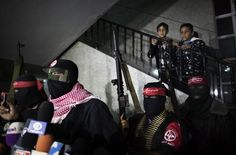 Palestinian children watch on as a spokesperson for the Abu Ali Mustafa wing of the Popular Front for the Liberation of Palestine (PFLP) addresses a press conference in Gaza City November 13, 2012. The PFLP alongside armed wings from the Democratic Front for the Liberation of Palestine (DFLP) and the Popular Resistance Committees (PRC) took responsibility for firing 11 rockets at southern Israel on November 12. (MARCO LONGARI - AFP/Getty Images)