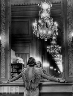 A model, wearing a gown trimmed in ostrich feathers, pauses to regard herself in the grand mirror of the Molyneux atelier, circa 1934.