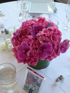 Matching low centerpiece in a cylinder with a leaf-wrap treatment, hydrangea and phaleonopsis orchids by Starbright Floral Design