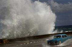 A driver maneuvers his classic American car along a wet road as a wave crashes against the Malecon in Havana, Cuba, Thursday, Oct. 25, 2012. Hurricane Sandy blasted across eastern Cuba on Thursday. (AP Photo/Ramon Espinosa)