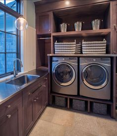 This laundry room would make anyone excited to wash clothes!  The side by side washer and dryer are built up to a comfortable height, but instead of pedestals, decorative storage baskets were used.  This makes the room feel more custom!  The dark wood is exquisite and we love the stainless countertops and sink.  The #kohler Bellera faucet is a great faucet for all of your washing needs!