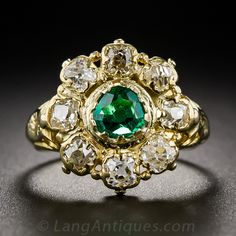 This early-Victorian jewel centers on a bright crystalline-green emerald orbited by eight antique cushion-cut diamonds. The gemstones are set in decoratively fashioned collet settings supported by scrolled and engraved shoulders. A rare and delicate antique beauty not recommended for rugged everyday wear