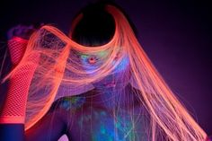 Woman wearing UV contacts, with UV makeup and hair, real shot under black light  Stock Photo
