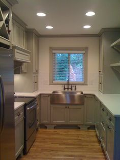 light-medium gray cabinets, light countertops, white walls, medium wood floors, stainless appliances