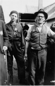 A father and son, wearing a Jewish badge, in front of their machine shop in the Debrecen ghetto. 1944.