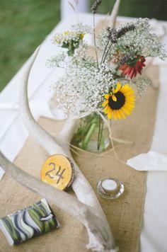 Mason jar wedding centerpiece with mini sunflowers atop burlap runner. - I like the bleached antler