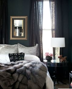 Dark walls, light linens & a faux fur throw make for an incredibly cozy bedroom.