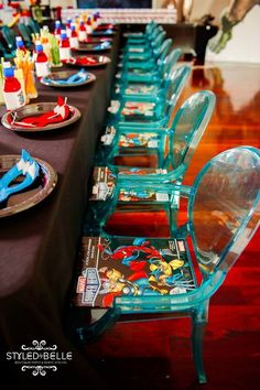 """Avengers: Dining Area: Each place setting included an Avenger coloring book, colorful """"power juice"""" wrapped in printable wrappers and a super hero mask. Glasses filled with colorful veggies lined the center of the table."""