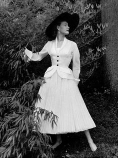 1951 Model in white pleated organdy dress, bodice is Valenciennes lace, jacket is fitted with shawl collar and pockets, by Jacques Fath