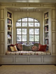 Window seat flanked by bookshelves -