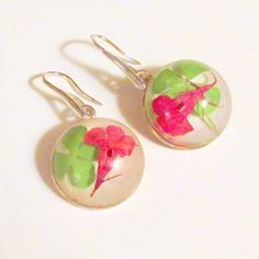 Genuine, natural four leaf clover earrings with a splash of pink from pink petals have a feeling of good fortune about them.