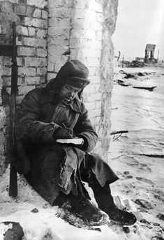 Soviet soldier, sitting in the ruins of Stalingrad, writes a letter to the folks back home upon the end of the battle, January 1943.
