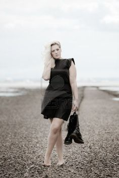 barefoot woman on a stoney beach wearing a dress and holding boots posing Stock Photo