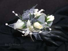 Wrist Corsage - assorted white flowers accented with blue thistle and pearl spray.