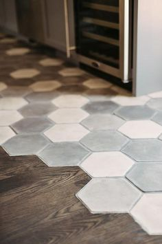 Fantastic gray kitchen features a white and gray hex concrete tiled floor which seamlessly transitions into a stained oak wood floor which leads to the dining space.