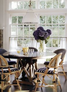 Victoria Hagan, sunlit breakfast room with cafe chairs and pretty purple hydrangea.