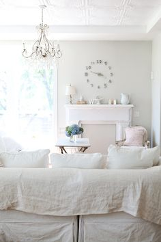 I love the slipcovered couch, chandelier, tin ceiling and the sunlight!
