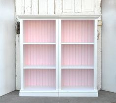 Use painted wainscoat and trim pieces to dress up a cheap bookshelf.