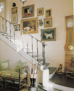 """Nice stairway design, with country French """"Comtoise"""" """"wag on wall"""" clock in a pine case, with a nice old bench, umbrella holder and nice looking artwork going up the stairway wall."""