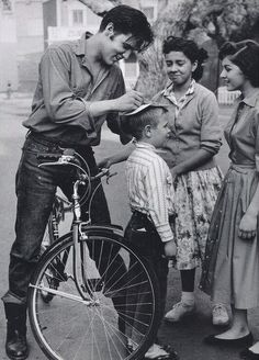 Elvis signs autographs for fans while on a bike ride