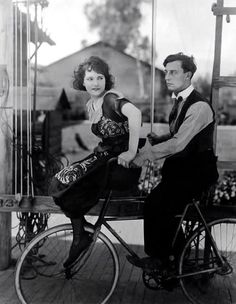 Buster Keaton and Sybil Seely ride a bike.