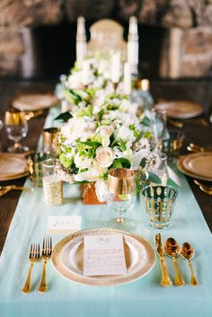 Gold cutlery, plates, glasses, and centerpieces - all on top of a mint table runner #gold #mintgold #weddingdecor #tablescape #goldwedding