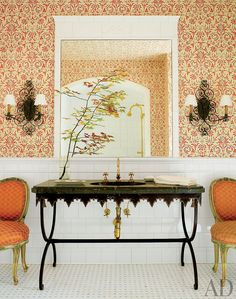 In a Virginia house, a bath features patterned wallpaper by Peter Fasano and a 19th-century French iron-and-marble sink from Treillage.