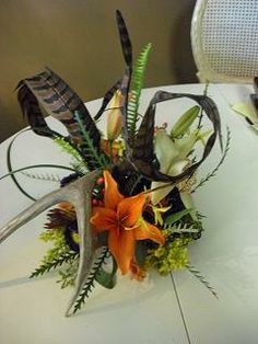 Centerpiece for a mans birthday party with a hunting theme.  Complete with antlers and feathers.