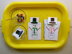 sorting buttons by color onto snowpeople using tweezers