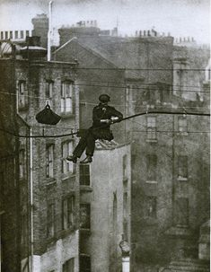 London in the 1920's-telephone engineer, 50 feet up. The engineer is attaching the main telephone cable to a new support wire, suspended between Maddox Street and Conduit Street in Mayfair.