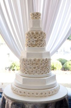 This towering wedding cake features alternating layers of quilted fondant and swirled sugar rosettes.