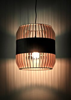 Lath Lamps are a series of vertically slatted lamps designed by the Montreal-based Jonathan Dorthe for Atelier-D. The lamps are made from thin, laser-cut plywood that are then wrapped with horizontal bands of dark leather or wood veneer.