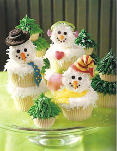 Frosting The Snowmen: Stacked cupcakes with tops rolled in coursely shreaded coconut. The trees are stacked as well, & are made with a star tip as you layer the buttercreme on top of itself. The snowmen's accessories are made with colored fondant / By ~christmas-cupcakes on deviantART