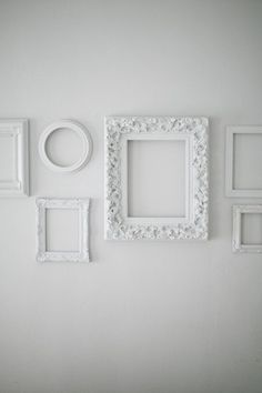 white frames on a white wall. Insert art works hung on string.