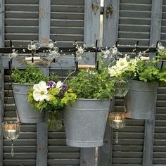 Aluminium pots, flowers and hanging candles - so pretty for a garden!