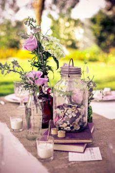 pretty centerpiece for a garden table. blooms, burlap, bottles, buttons.