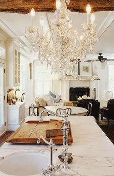Carrara marble, crystal chandelier, wood beamed ceilings, and French Country style.