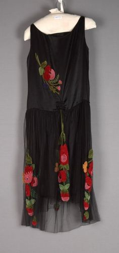 Circa 1928 scoop necked sleeveless bodice of black satin, skirt from low waist of netting over satin. Embroidered on Right bodice and skirt with large polychrome bouquets of chenille flowers. Via Fine Arts Museums of San Francisco.