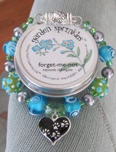 Forget-Me-Not Pet-Lover Memorial Bracelet - Auntie Angel Designs - and forget-me-not flower seeds.  Paw print heart charm and blue flower charm on the reverse.  $55.00, with a donation to charity/shelter/cause of customer's choice.   So sweet!