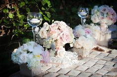 collection of blush colored florals arranged in silk fabric and lace wrap for escort table